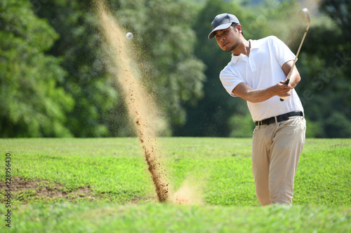Deurstickers Golf Young Asian man golfer hitting a bunker shot