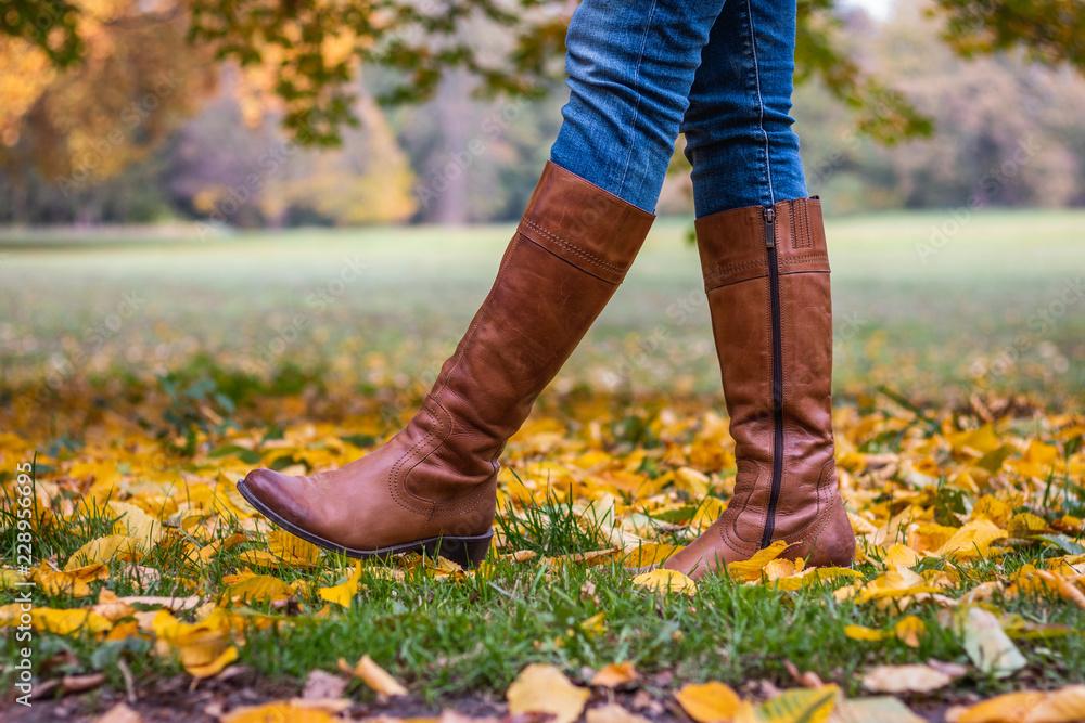 Fototapeta Woman wearing brown leather boot and walking in fallen leaves. Fashion model in autumn park