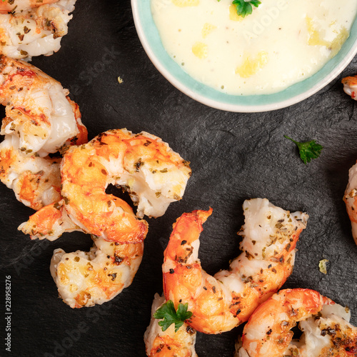 A closeup photo of cooked shrimps on a black plate with a sauce bowl
