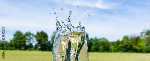 Fotografía  Spritzendes Wasser aus Glas auf Natur Hintergrund - Getränk