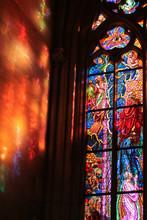 Raggi Di Sole Si Riflettono Attraverso La Vetrata, In Stile Gotico E Decorata Con Motivi Religiosi Policromi, Sulla Parete Accanto Creando Un Effetto Incantevole E Suggestivo