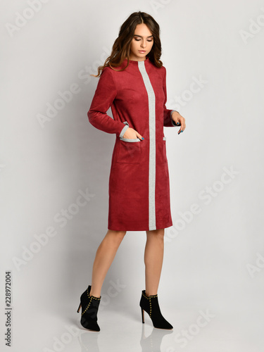 Young beautiful woman posing in new dark red fashion winter dress coat on high hills full body  Wall mural