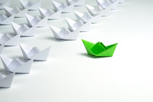 Leadership Concept With Green Paper Ship Standing Out From The Group Of White Ships On White Background.