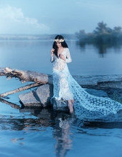 A Nymph With Long Dark Hair In A White Vintage Dress Sits On A Log Across The River. In The Hair A Wreath Of Lilies. Fantasy Photosession, Artistic Processing In Cold Blue Tones