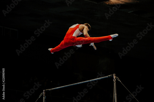 Spoed Fotobehang Gymnastiek athlete gymnast exercise on horizontal bars in gymnastics