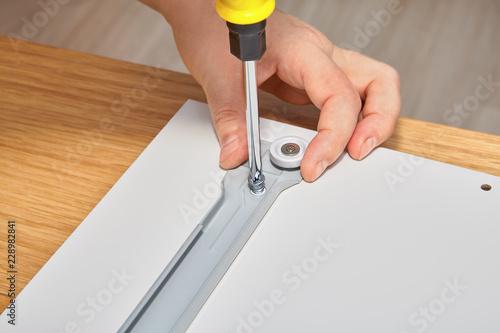 Joiner is mounting slide bracket for drawer using screwdriver.