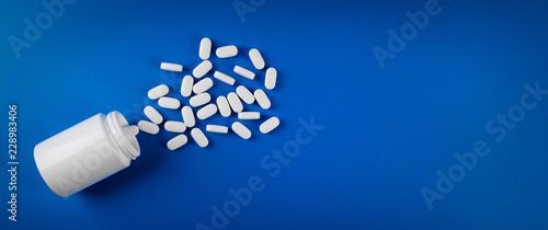 medical pills on blue background. top view copy space