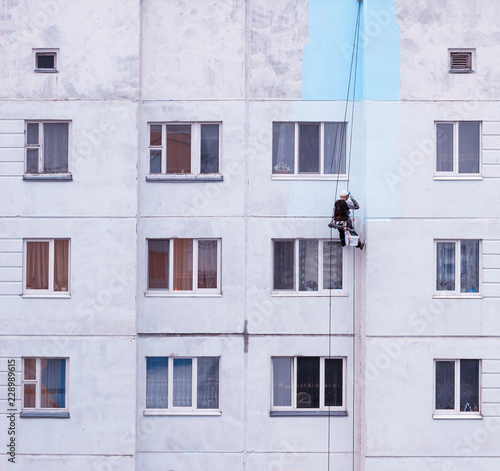 Fotografiet  A worker climber paints a residential high-rise building and seals up joints in
