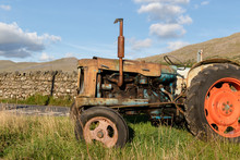 Side View Of An Old Abandoned Rusty Agricultural Tractor In A Grass Field