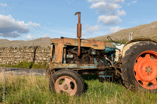 Pinturas sobre lienzo  Side view of an old abandoned rusty agricultural tractor in a grass field