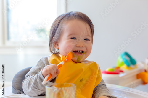 Happy toddler boy smiling while eating a meal Wallpaper Mural