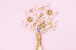 canvas print picture - Champagne bottle with christmas decoration from confetti stars, golden balls and party streamers on pink background. Flat lay style. .