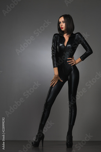 Photo  woman in latex suit on a dark background