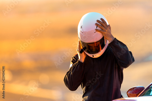 A Driver At Racing School Putting His Helmet On Before Taking His Car On To The Track.