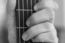 Male Hand Picks Up A Guitar Chord. Guitar Wrinkled Male Fingers Pinch The Strings On A Black Fingerboard. Black And White Photo Of Playing The Guitar. Accord C Major 7.