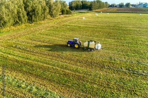 Tractor making hay bails. Wallpaper Mural