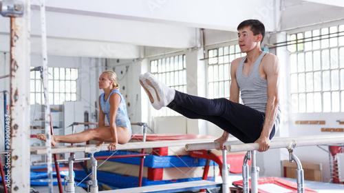 Foto auf Leinwand Gymnastik Man gymnast training gymnastic action at steel bars in gym, woman on background