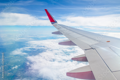 Deurstickers Vliegtuig Wing plane with white cloudy and blue sky,