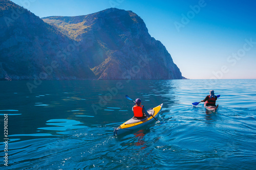 Kayaking. People swim in the sea kayak near the mountains. Adventures on the water