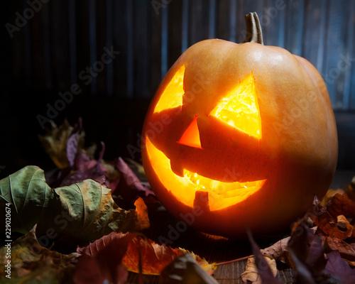 Jack o lanterns Halloween pumpkin face on wooden background Wall mural