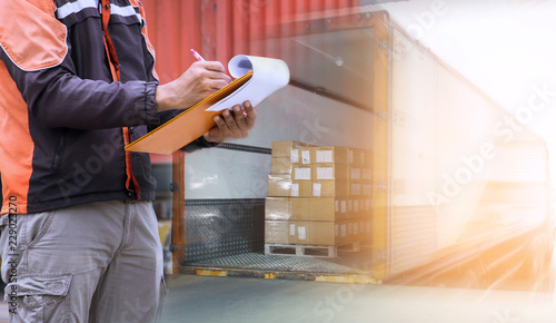 Fotomural Warehouse worker holding clipboard with control loading shipment goods into container truck