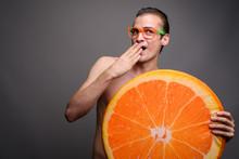 Surprised Man Shirtless Holding Big Slice Of Orange Fruit