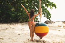 Young And Sexy Woman Is Posing Beside Swings Made From Old Buoy