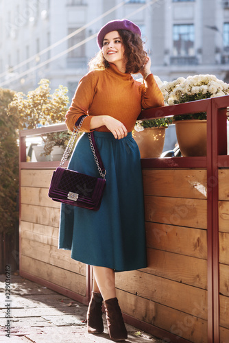 Outdoor full body fashion portrait of young beautiful woman wearing stylish  beret, orange turtleneck, midi green blue skirt, ankle boots, holding quilted purple bag, posing in street of european city Wall mural