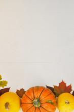 Yellow And Orange Pumpkins And Autumn Leaves On White Wooden Background For Harvest Fall And Thanksgiving Theme.