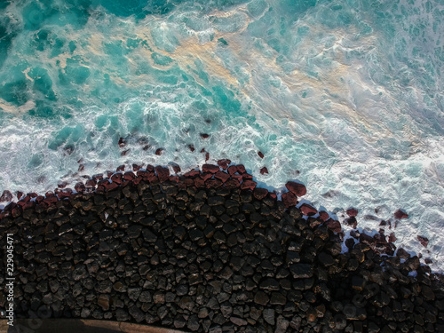 Foto op Canvas Poort Aerial top view of sea waves hitting a stones from a jetty in pier. Drone view