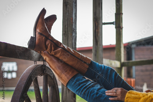 Fotografia, Obraz  Woman is relaxing on the ranch with her legs on a wooden railing