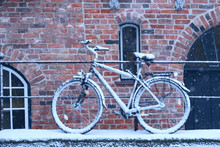 Winter Day In City. Snow Covered Bicycle Parked On Streen