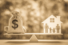 Legacy / Inheritance Or Death Tax Concept : US Dollar Bag, A House And Family Members E.g Father, Mother, Son, Daughter On A Balance Scale, Depicts A Tax Paid By Person Who Inherits Money Or Property.