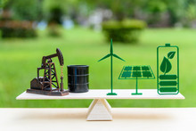 Fossil Fuel Vs Renewable / Future Clean Alternative Energy Concept : Petroleum Pumpjack, Crude Oil Drum Barrel, Solar Panel, Green Leaf Battery, Wind Turbine On A Wood Balance Scale In Equal Position.