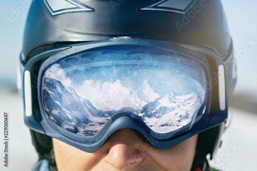 obraz PCV Close up of the ski goggles of a man with the reflection of snowed mountains. A mountain range reflected in the ski mask. Man on the background blue sky. Wearing ski glasses. Winter Sports.