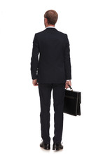 Rear View Of Businessman In Suit Holding Suitcase And Standing