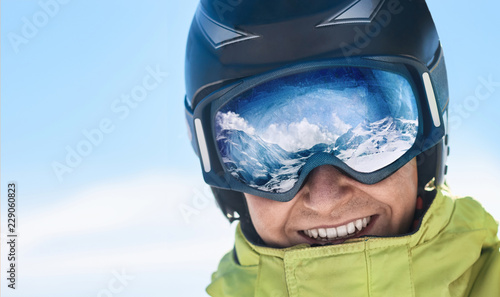 Close up of the ski goggles of a man with the reflection of snowed mountains.  A mountain range reflected in the ski mask.  Man  on the background blue sky. Wearing ski glasses. Winter Sports.