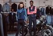 Two stylish elegantly dressed men standing near retro sports motorbike at the men's clothing store.
