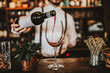 canvas print picture - Close up shot of a bartender pouring red wine into a glass. Hospitality, beverage and wine concept.