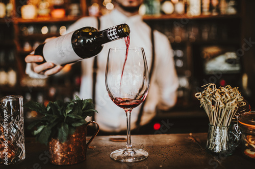 Photo sur Toile Vin Close up shot of a bartender pouring red wine into a glass. Hospitality, beverage and wine concept.