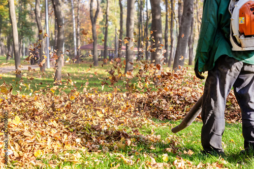 Photo Worker operating heavy duty leaf blower in city park