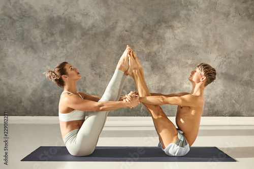 Fotografie, Obraz  Athletic young couple practicing partner yoga at gym, sitting on one mat facing each other, bringing heels together and holding hands, doing Navasana or Boat Pose