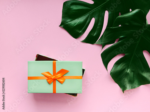 Photo  Palm leaves Close-up photo in flat lay Small green gift box and leaves of monste