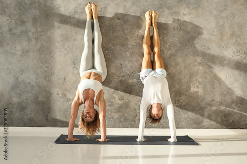 Valokuva Young athletic barefoot man and woman doing handstand against wall in light training hall