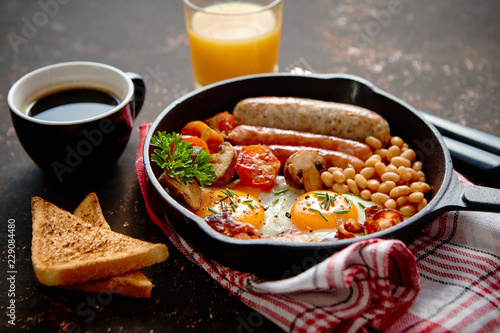 Fototapeta Full English breakfast - fried egg, baked beans, bacon, sausages on a dark rusty background, toasts, orange juice and coffee on a side. Dish in iron frying pan. obraz