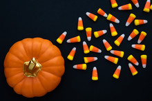 Orange Ceramic Pumpkin With A Gold Stem On A Black Background, With Scattered Candy Corn On The Background