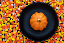 Black Ceramic Plate And Orange Ceramic Pumpkin Sitting On A Background Of Halloween Candy Corn