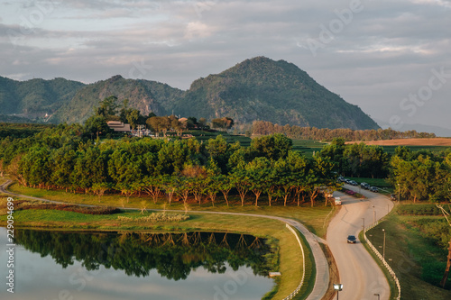 Staande foto Donkergrijs Beautiful landscape with high mountain , reflection in mountain lake, blue sky and yellow sunlight in sunrise, rural road. Singha Park, Chiang Rai, North of Thailand