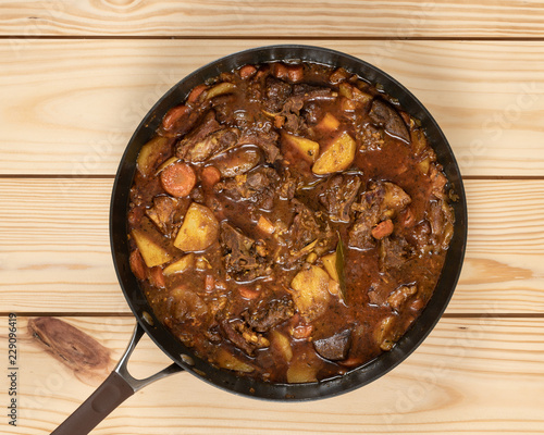 Close-up of colorful goat stew in cooking pan on top of  wooden table.