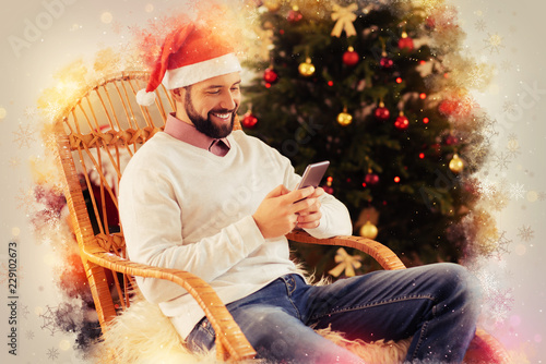 Near Christmas tree. Successful handsome bearded businessman feeling relaxed sitting in his chair near Christmas tree at home
